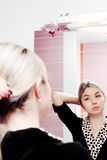 Young blonde woman looking to mirror and combing her hair Royalty Free Stock Photography