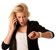 Young blonde woman looks at her watch when she is being late iso stock photos