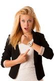 Young blonde woman looks at her watch when she is being late iso stock images
