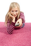 Young blonde woman lying on the pink carpet with remote control stock images