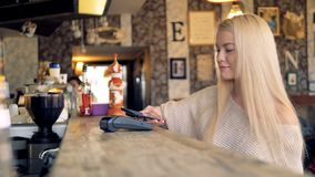 A young blonde woman makes a NFC transaction. A young pretty woman pays in a cafe using her smartphone stock footage