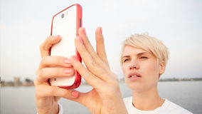 Young blonde woman makes selfy Royalty Free Stock Photography
