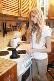 Young blonde woman making coffee Stock Images