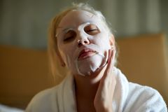 Young blonde woman making facial sheet mask. Beauty and skin care concept stock image