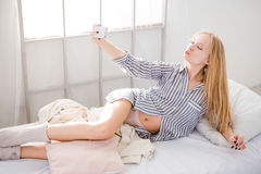 Young blonde woman making self photos with mobile phone Stock Photos