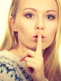 Young blonde woman making silence gesture. Gestures and signs concept. Young blonde woman making silence gesture with finger close to her mouth stock image