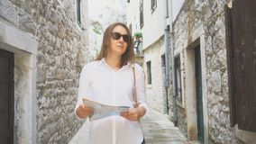 Woman with a map. Young blonde woman with a map in the street stock video