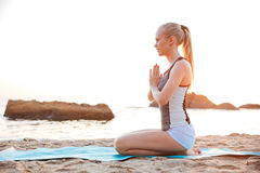 Young blonde woman meditating on the beach Stock Image