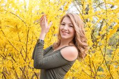 Young blonde woman near blossoming yellow trees in spring park on sunny day. Beautiful happy girl enjoying smell in a royalty free stock photo