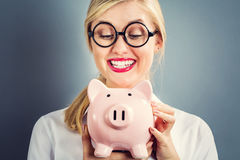 Young blonde woman with a piggy bank Royalty Free Stock Photo