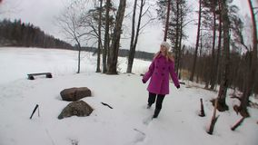 Young blonde woman in pink coat running in winter forest stock video footage