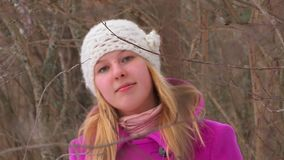 Young blonde woman in pink coat walking in winter forest stock video