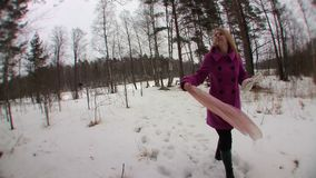 Young blonde woman in pink coat walking in winter forest stock video footage