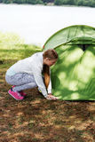 Young blonde woman pitching a tent. Royalty Free Stock Images
