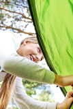 Young blonde woman pitching a tent. Stock Photo