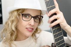 Young blonde woman playing the acoustic guitar Royalty Free Stock Photo