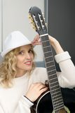 Young blonde woman playing the acoustic guitar Royalty Free Stock Image