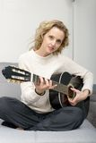 Young blonde woman playing the acoustic guitar Royalty Free Stock Photography