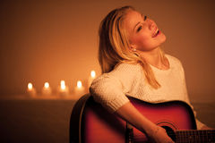 A Young blonde woman playing guitar in candle light Royalty Free Stock Images