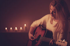 Young blonde woman playing guitar in candle light Royalty Free Stock Image