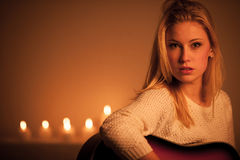 Young blonde woman playing guitar in candle light Royalty Free Stock Photos