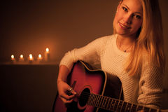Young blonde woman playing guitar in candle light Stock Images