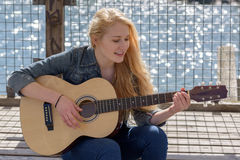 Young blonde woman playing guitar on a lake Royalty Free Stock Photo