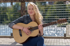 Young blonde woman playing guitar on a lake Royalty Free Stock Images