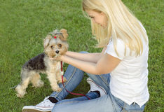 Young blonde woman playing with her dog Stock Photo
