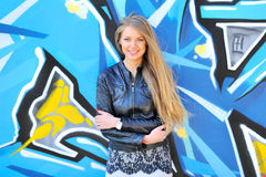 Young blonde woman posing. Beauty young blonde woman posing in front of colorful grafitti stock photography