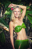 Young blonde woman posing with banana leaves Stock Images