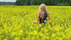Young blonde woman posing in beautiful rapeseed field stock footage