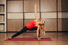Young blonde woman practicing yoga,-Virabhadrasana Rotated warrior pose Royalty Free Stock Image