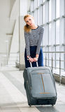 Young blonde woman pulling heavy suitcase on the station was going on a trip. It is difficult to carry luggage. Tired Stock Photos