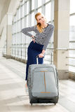 Young blonde woman pulling heavy suitcase on the station was going on a trip. It is difficult to carry luggage. Tired Royalty Free Stock Photo