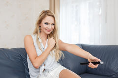 Young blonde woman pushing button on remote control at home. In living room stock photography