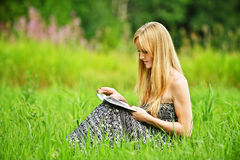 Young blonde woman reading book Royalty Free Stock Photos