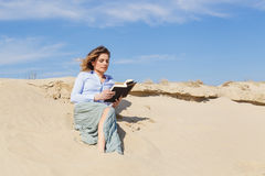 Young blonde woman reading a book on the beach. Attractive young blonde woman reading a book on the beach Stock Photo