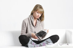 Young blonde woman reading book on sofa Royalty Free Stock Photos