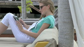 Young blonde woman reading e-book in tropical resort. Woman relaxing on luxury beach. stock footage
