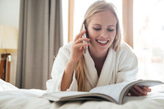 Young blonde woman reading magazine and talking on phone Stock Image