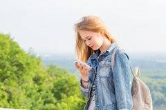 Young blonde woman reading a message that came to the smartphone in nature. Internet, technology royalty free stock photography