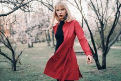 Young blonde woman goes for walk in spring garden on background of blossoming trees. Royalty Free Stock Photography