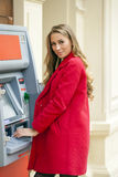 Young blonde woman in a red coat withdraw cash from an ATM in th. Young blonde woman in a red coat withdraw cash from an ATM in a shopping center Royalty Free Stock Image