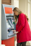 Young blonde woman in a red coat withdraw cash from an ATM in th. Young blonde woman in a red coat withdraw cash from an ATM in a shopping center Royalty Free Stock Photography