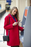 Young blonde woman in a red coat withdraw cash from an ATM in th. Young blonde woman in a red coat withdraw cash from an ATM in a shopping center Stock Images