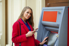 Young blonde woman in a red coat withdraw cash from an ATM in th. Young blonde woman in a red coat withdraw cash from an ATM in a shopping center Stock Photo