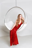 Young blonde woman in red dress holding a glass of white wine sitting in transparent chair against wall with geometric Royalty Free Stock Image
