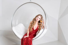 Young blonde woman in red dress holding a glass of white wine sitting in transparent chair against wall with geometric Stock Photos