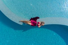 Young blonde woman in red dress lying in the swimming pool stock image